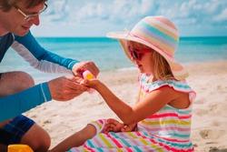 sun protection - dad put suncream on little girl face at beach