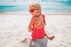 sun protection- happy little girl with suncream at beach