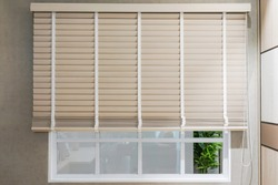 Sun-protection jalousie of white color on the window in a bright sunny day