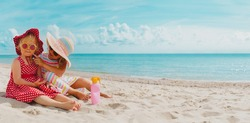 sun protection- little girls with suncream on beach