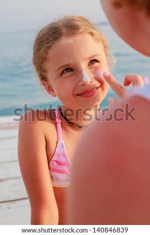 Sun protection. Mother anoints her daughter face protective cream on the beach