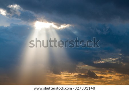 sun ray light through down from rain cloud during sunset time