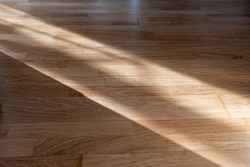 Sun ray or beam on wooden floor, sunlight lines shadow on parquet, interior with sunlight