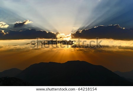 Sun rays at sunset in the clouds on the mountains
