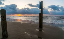 Sun rays beam out from awe inspiring sunrise on Padre island beach Port Aransas , Texas , shoreline with old pier pylons sticking up out of the sand