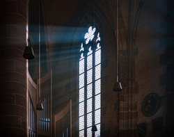 Sun rays beaming through the old stained glass window of Nurnberg cathedral in Bavaria, Germany, Europe.