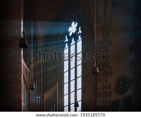 Sun rays beaming through the old stained glass window of Nurnberg cathedral in Bavaria, Germany, Europe. stock photo