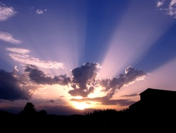 Sun rays between clouds, at dusk