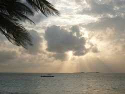 Sun rays breaking through the clouds at sunset on the beach and a motorboat on the sea