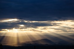 sun rays breaking through the clouds over a mountain landscape