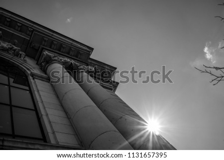 Sun rays, caused by diffractions from one of the columns of the building of the Sofia University, Bulgaria, moody image in black and white with clear sky in a sunny day