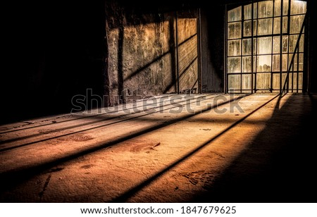 Sun rays fall through tall windows into an abandoned dusty room. Sunlight window in darkness. Dark sunlight window. Tall window sunlight