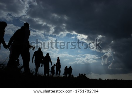 Sun rays illuminate people. Immigration of people. Blue sky with dark clouds Foto stock ©