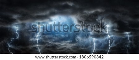 Sun rays in the gap between the clouds and sparkling lightning in the dark sky.  Concept on the theme of weather, natural disasters, storm, typhoons, tornadoes, thunderstorms, zipper, lightning.