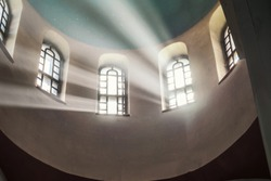 Sun rays make their way through the high vaulted arched window under dome in church temple Concept religion enlightenment light and dark