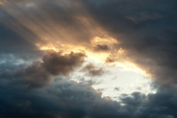 Sun rays of the setting sun through the clouds. Low angle view of cloudy sky during sunset.