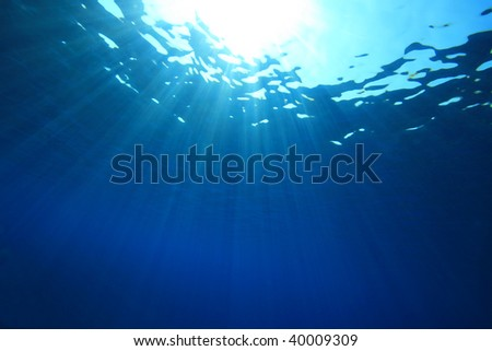 Sun rays on blue water background