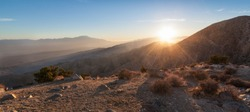 Sun rays over mountain range in desert. This is a panorama image taken of Keys View in Joshua Tree National Park in California at sunset. The last sun rays hover over the mountainous desert landscape.