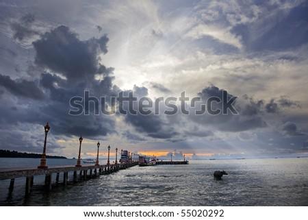 Sun rays shining through spectacular clouds over ocean - stock photo