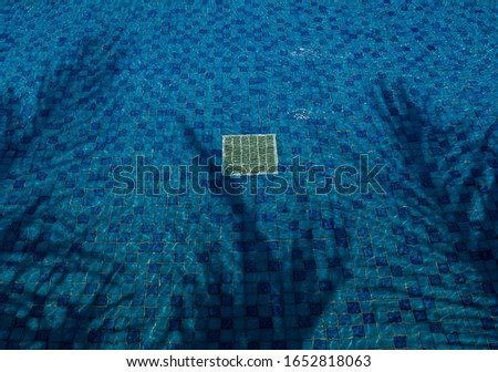 Sun reflection in clear clean and bright blue water surface of swimming pool. silhouettes shadow tree on the water