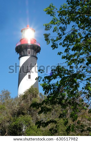 Shutterstock Sun reflects from the lantern pane of the black and white striped St Augustine Light Station with red cupula.  St Augustine Lighthouse on a clear day with blue sky and no clouds.