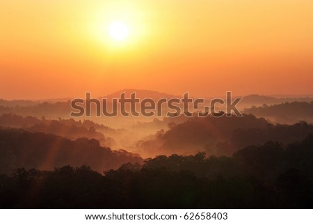 sun rise over a fog and mountain - stock photo