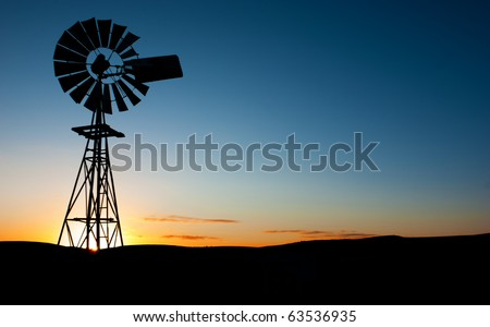 Sun rises behind a windmill - stock photo