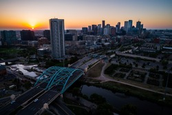 Sun rises over horizon in the mountain town of Denver , Morning Sunrise in the Mile High City of Denver , Colorado , USA golden hour Traffic and gorgeous sunshine aerial drone view above bridges