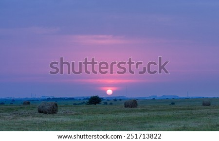 Sun rising above protected area of Yamskaya Steppe with stacks of harvested hay, Belgorod region in southern Russia