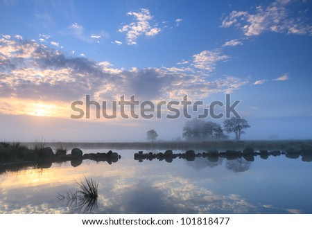 Sun rising above the fog near a lake in nature area 'De Onlanden' in Drenthe, the Netherlands.