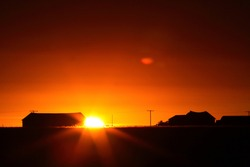 Sun rising behind a Saskatchewan farm building