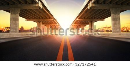 sun rising behind perspective on bridge ram construction and asphalt road perspective to ship port background use for infra land and vessel transportation