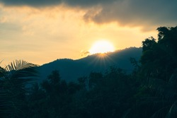 Sun rising from behind the mountain top over the valley with forest and palm trees on a tropical island