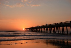 Sun rising over horizon and pier, beach illuminated with sunlight, Jacksonville Florida, USA.