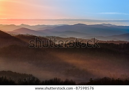 Sun rising over snowy mountains of Smokies in early spring with fog in the valleys