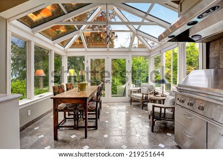 Sun-room patio area with transparent vaulted ceiling, steel barbecue with hood and dining table set