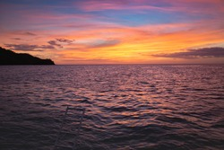 sun set in costa rica from the back of a dive boat with colorful sky