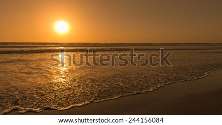 Sun sets over horizon of ocean. Surf on sandy beach. Sky, water and shore in the evening painted in orange, gold color.