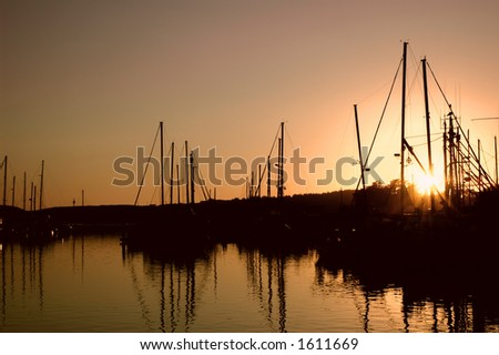 Sun setting behind a oceanfront marina - stock photo