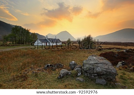 Sun setting behind Buachaille Etive Mor with Black Rock cottage and boulder in foreground. Photographed in Glencoe, Scotland