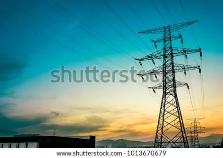 Sun setting behind the silhouette of electricity pylons ストックフォト ©