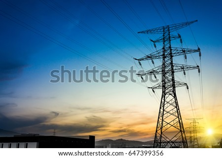 Sun setting behind the silhouette of electricity pylons #647399356