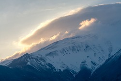 Sun setting behind the slope of Mt. Damavand, the highest stratovolcano in Asia. Partly cloudy afternoon in the mountains of Iran. Cap clouds gather near the summit. Persia.