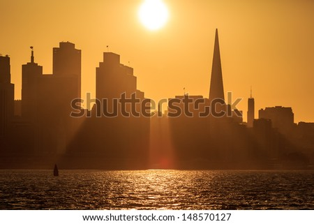 Sun setting directly in gap of skyline behind San Francisco casts golden reflections and shadows into bay.