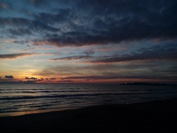 Sun setting in winter behind the clouds coloring them black and pink in the Adriatic sea Durres beach, Albania. Sun rays shine the tallest building in Durres city.