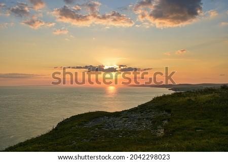 Sun setting on the horizon across the sea at St Aldhelm's Head along the south west coastal path along the Jurassic coastline towards Chapmans pool in Dorset. Zdjęcia stock ©
