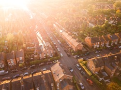 Sun setting over a traditional British neighbourhood. Lens flare and warm colours to give a homely effect.