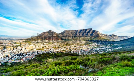 Sun setting over Cape Town, Table Mountain, Devils Peak, Lions Head and the Twelve Apostles. Viewed from the road to Signal Hill at Cape Town, South Africa #704365027