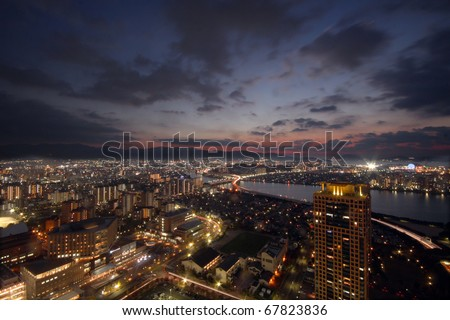 Sun setting over city with light up buildings in Japan