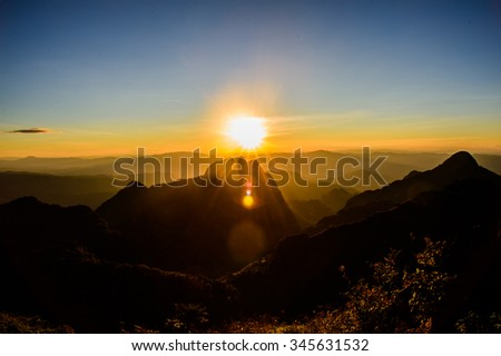 Sun setting over hills in Thailand